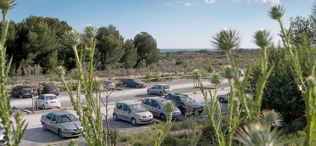 Le très poussièreux parking du Lido de Carnon, avec de nombreux trous dans la route d'accès.