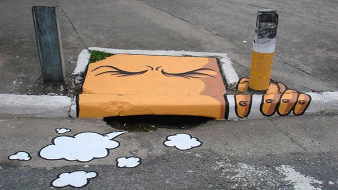 Street Art : Bouche d'égout peinte en fumeur qui toussote avec un poteau métal repeint en cigarette