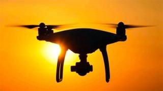 Un drone munie d'une caméra vole dans le ciel couchant