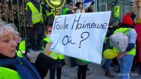 Une femme gilets jaunes montre une pancarte devant les grilles de la préfecture de Nimes