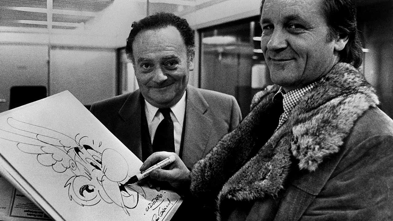 René Goscinny devant un dessin que Albert Uderzo termine de dessiner